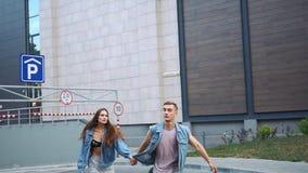 Mężczyzna i kobieta ubieraliśmy w przypadkowym ulica stylu biegającym na ulicie zbiory wideo