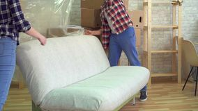 Mężczyzna i kobieta usuwamy ceratę od kanapy po tym jak poruszający wolny mo zdjęcie wideo