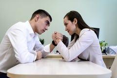 Mężczyzna i kobieta w biura odzieżowym zapaśnictwie na ręce przy biurkiem w biurze obraz royalty free