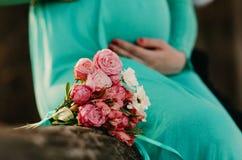 Mężczyzna i kobieta w ciąży w czerwieni sukni trzymamy ręki na brzuchu na lekkim tle fotografia stock