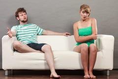 Mężczyzna i kobieta w nieporozumienia obsiadaniu na kanapie Zdjęcia Stock