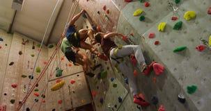 Mężczyzna i kobieta wspina się sztuczną ścianę przy bouldering gym 4k zbiory