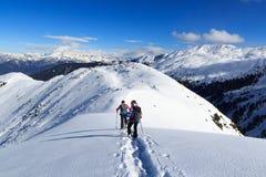 Mężczyzna i kobieta wycieczkuje na karplach i halnej śnieżnej panoramie z niebieskim niebem w Stubai Alps Obrazy Royalty Free