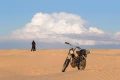 Mężczyzna i kobieta z motocyklem w pustyni przeciw chmurnego nieba tłu Zdjęcie Stock