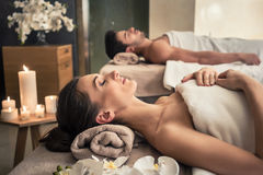 Mężczyzna i kobiety łgarski puszek na masaży łóżkach przy Azjatyckim wellness cente fotografia stock