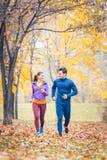 Mężczyzna i kobiety bieg jako sprawność fizyczna sport w jesień parku obraz royalty free