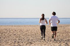 Mężczyzna i kobiety bieg w plaży Zdjęcie Royalty Free