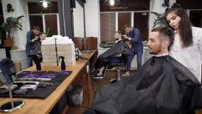 Mężczyzna i kobiety fryzjery męscy robić ostrzyżeniu na męskich modnisiów klientach zdjęcie wideo