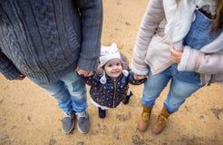 Mężczyzna i kobiety mienia ręki szczęście mała dziewczynka obrazy stock