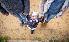 Mężczyzna i kobiety mienia ręki szczęście mała dziewczynka obrazy royalty free