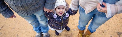 Mężczyzna i kobiety mienia ręki szczęście mała dziewczynka fotografia stock