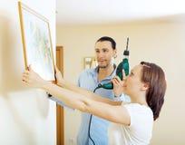 Mężczyzna i kobiety obwieszenie   obrazek w domu Fotografia Stock