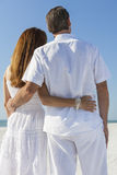 Mężczyzna i kobiety pary obejmowanie na plaży Zdjęcia Stock