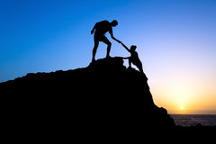 Mężczyzna i kobiety pomocy sylwetka w górach Obrazy Royalty Free