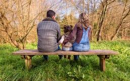 Mężczyzna i kobiety przytulenia małej dziewczynki obsiadanie na ławce zdjęcie royalty free