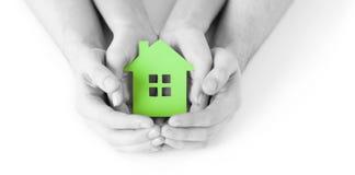 Mężczyzna i kobiety ręki z zielonego papieru domem Zdjęcia Stock