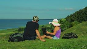 Mężczyzna i kobiety turyści przegapia jezioro siedzą na krawędzi góry kobieta otwiera laptop zbiory wideo