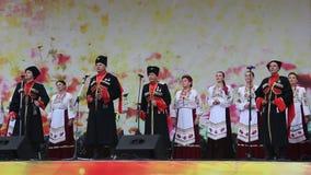 Mężczyzna i kobiety w kozaczku odziewają na scenie zbiory
