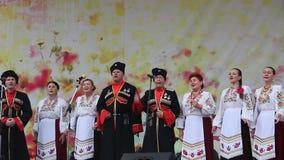 Mężczyzna i kobiety w kozaczku odziewają na scenie zbiory wideo