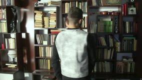 Mężczyzna i młoda dziewczyna wybiera książkę czytać Dwa ludzie patrzeje dla książek w bibliotece Ucznie szuka dla informaci zbiory wideo