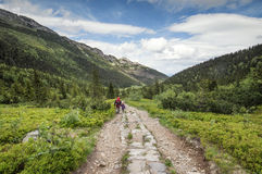 Mężczyzna i mała dziewczynka iść na halnym śladzie między dwa pasmem górskim Fotografia Royalty Free