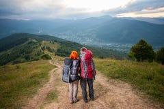 Mężczyzna i miedzianowłosa kobieta na drodze w górach Fotografia Royalty Free