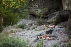Mężczyzna i pies Miniaturowy Schnauzer blisko jaru Enjoing czas outside Zieleni drzewa i góry na tle Obraz Royalty Free