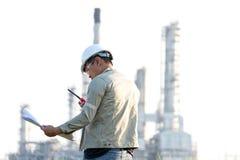 Mężczyzna inżynier czyta rysunkowego papieru budowę dla plan pracy przy elektrownią, Zdjęcia Royalty Free