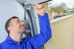 Mężczyzna instaluje garażu drzwi Obrazy Royalty Free