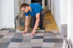 Mężczyzna instaluje podłogowe płytki zdjęcia stock