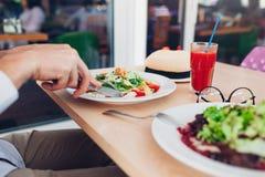 Mężczyzna je Caesar sałatki w restauraci Mieć smakowitego lunch pojęcia zdrowe jedzenie Fotografia Stock