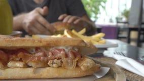 Mężczyzna je hamburger i francuz smaży przy kawiarnią Unhealhty jedzenie zbiory
