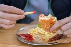 Mężczyzna je hamburger w fast food ulicy gościu restauracji zdjęcia royalty free