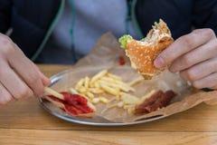 Mężczyzna je hamburger w fast food ulicy gościu restauracji fotografia stock