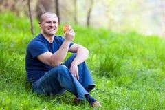 Mężczyzna je jabłka plenerowego Obrazy Royalty Free