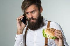 Mężczyzna je szybkie żarcie fr z brodą w białych suspenders i koszula fotografia royalty free