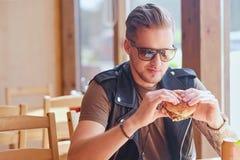 Mężczyzna je weganinu hamburger fotografia stock