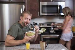 Mężczyzna je zboża podczas gdy dama robi śniadaniu Zdjęcia Stock