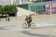 Mężczyzna jedzie bicykl głowa samochód niesie dziecka Zdjęcie Stock