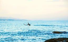 Mężczyzna jedzie małą motorową łódź w morzu obrazy royalty free