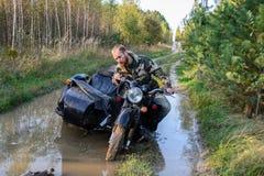 Mężczyzna jedzie motocykl z sidecar dostać zablokowanym na drodze w lesie zdjęcie royalty free
