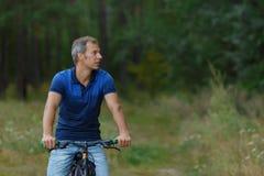 Mężczyzna jedzie na bicyklu w sosnowym lesie, sporta czas wolny Fotografia Stock