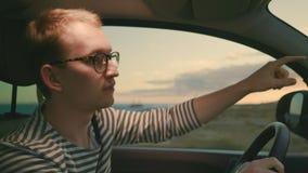 Mężczyzna jedzie samochód przeciw tłu południowy krajobraz w zmierzchów promieniach zdjęcie wideo