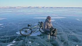 Mężczyzna jest odpoczynkowym obsiadaniem na kole bicykl na lodzie Pije herbaty od termos butelki Cyklista ubiera zdjęcie wideo