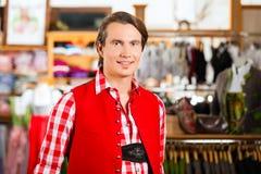 Mężczyzna jest próbuje Tracht lub Lederhosen w sklepie Obrazy Royalty Free