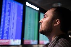 Mężczyzna jest przyglądającymi lotów przyjazdami i odjazdy wsiadają przy lotniskiem zdjęcie stock
