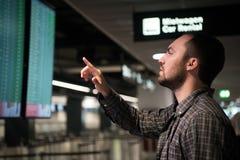 Mężczyzna jest przyglądającymi lotów przyjazdami i odjazdy wsiadają przy lotniskiem fotografia royalty free