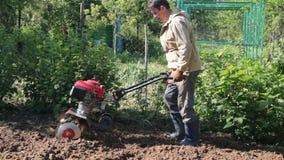 Mężczyzna jest rolnikiem w podmiejskim terenie, jarzynowy ogród, pługi ziemia z kultywatorem, manuału silnika pług, rzuca glinę i zdjęcie wideo
