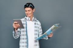 Mężczyzna jest ubranym hełmofony odizolowywających na szarości ściany turystyki pojęcia mienia mapy dopatrywania trwanim wideo na fotografia royalty free