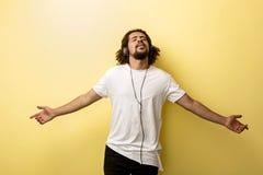 Mężczyzna jest ubranym hełmofony w otwartej ciało pozycji słucha muzyka z błogości wyrażeniem na twarzy Oczy są fotografia stock
